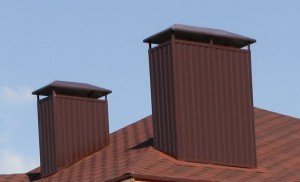 Дымоходы на крыше современного частного дома.