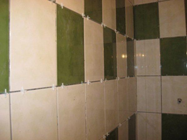 Бежевая и зеленая плитка в процессе установки