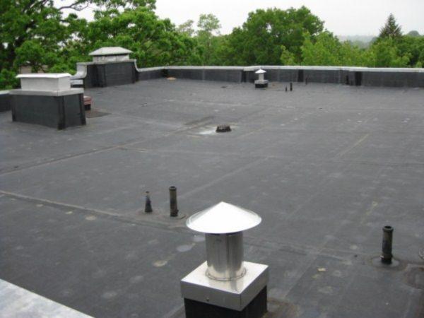 Фановые выводы канализации можно увидеть на плоской крыше многоквартирного дома.