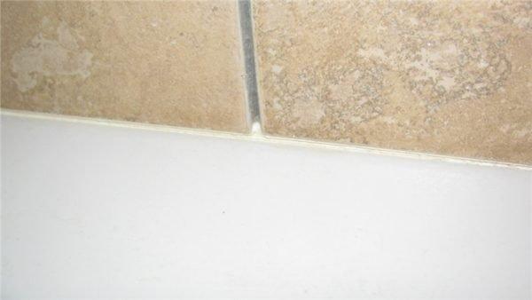Примыкание ванны к фартуку. Кафель нависает над ней небольшой полкой.
