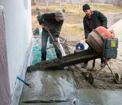 Процесс заливки отмостки бетоном.