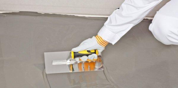 Раствор на цементной основе наносится шпателем и распределяется по поверхности пола.