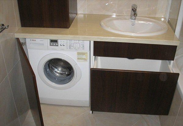 Шкаф для ванной для стиральной машины может быть оснащён дверцей, которая при необходимости полностью закрывает доступ к устройству
