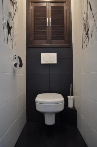 Шкаф в туалете над подвесным унитазом с инсталляцией.