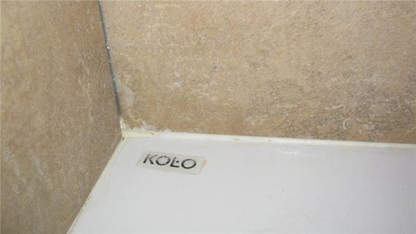 Стык ванны и стены заполнен белым герметиком.