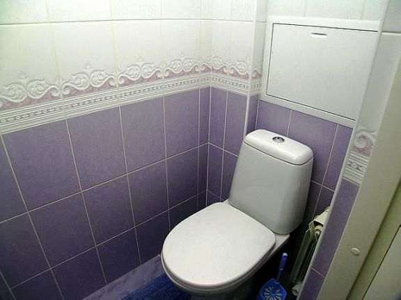 Туалет, отделанный кафельной плиткой.
