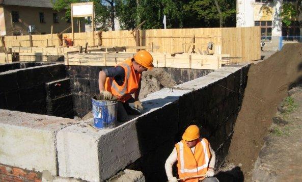 Грунтование бетонных блоков фундамента битумным праймером.