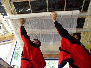 Монтаж пароизоляционной мембраны на балки потолка снизу.