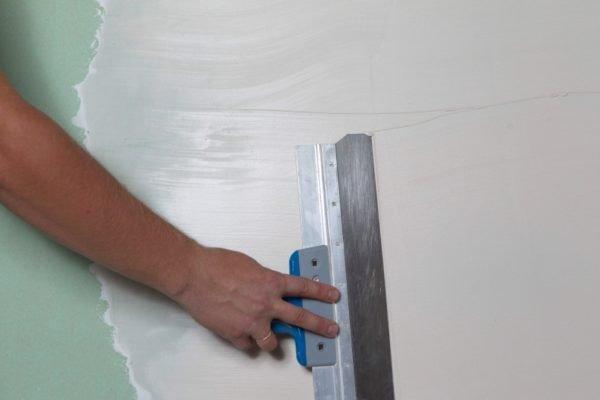 На фото – нанесение стартовой шпаклевки на стены