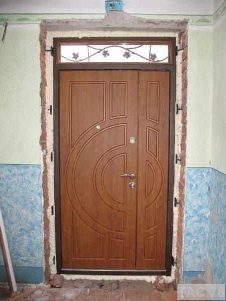 На фото показана задувка зазоров между коробкой и дверным проемом монтажной пеной.