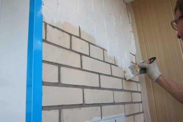 Нанесение грунта на стену.