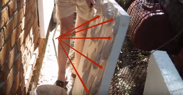 Нанесение клеевого раствора на плиту (на фото стрелками отмечен просвет, оставленный для выхода воздуха при приклеивании).