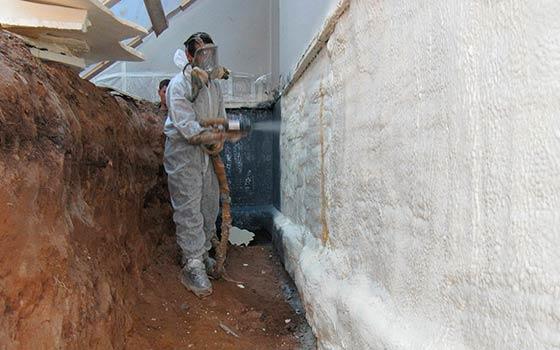 Напыление полиуретановой пены на подземную часть фундамента.