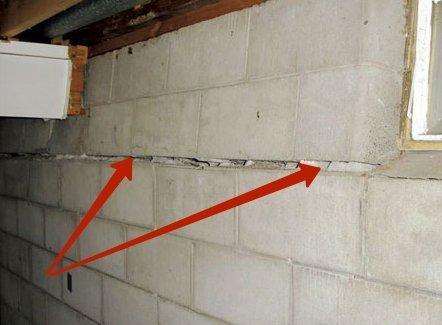 Обозначенные на фото трещины приводят не только к теплопотерям, но и угрожают целостности всего дома.