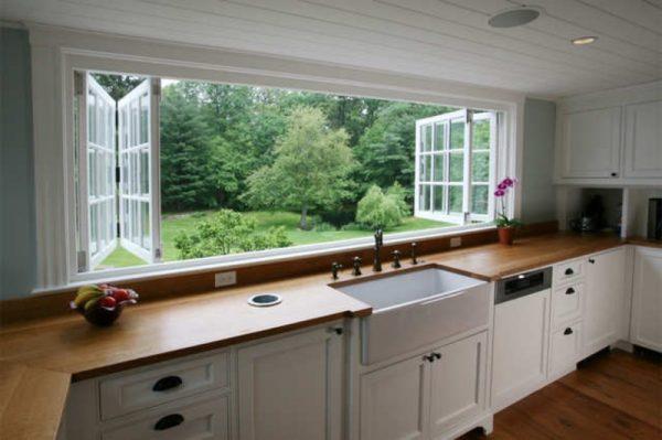 Широкое окно в кухне с панорамным видом на лесную поляну.