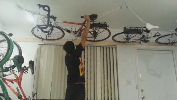 Велосипед поднимается к потолку и там фиксируется