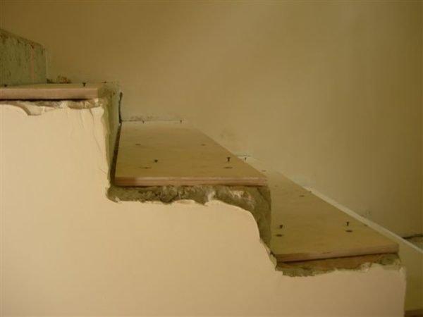Фанерная подложка на бетонной лестнице.