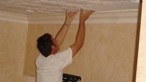 На фото – приклеивание плитки к потолку