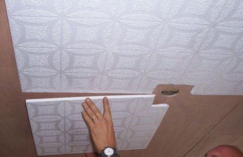 Процесс приклеивания плитки к потолку.
