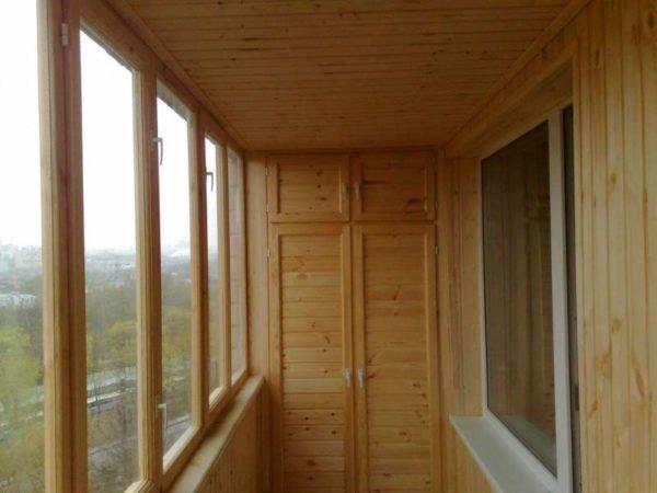 Если лоджия обшита деревянной вагонкой, то и фасад мебели желательно делать из того же материала.