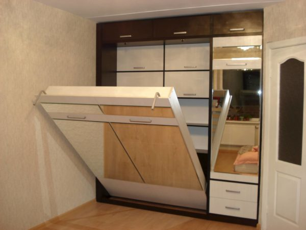 Фасад из ДСП с накладными зеркальными вставками — это распространённое решение, так как вписывается в большинство современных интерьеров, где наличие зеркал является обязательным элементом декора