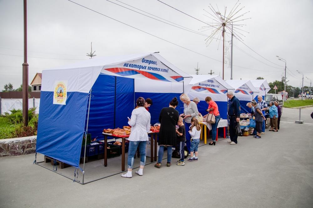 Фото торговых палаток с продавцом и покупателями.