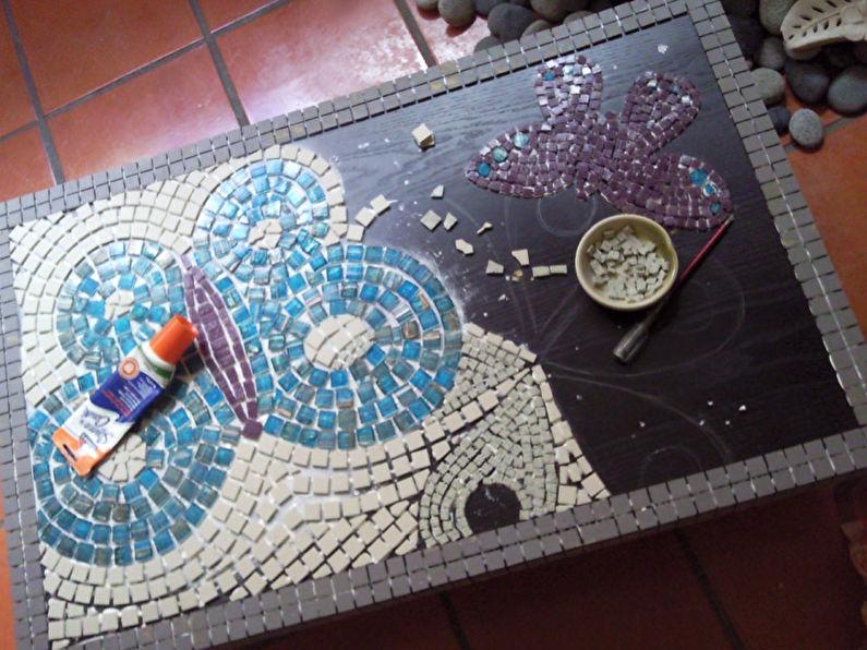На любительском уровне, при обустройстве мозаичного панно на старом столе, каждую плитку желательно клеить отдельно.