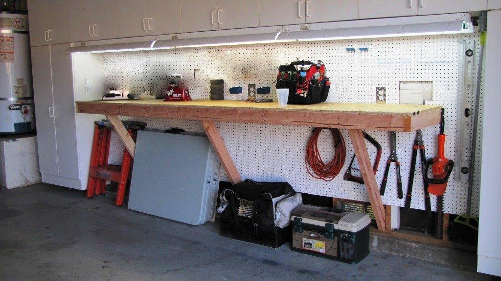 Рабочий стол в сочетании с инструментальными шкафами в интерьере гаража