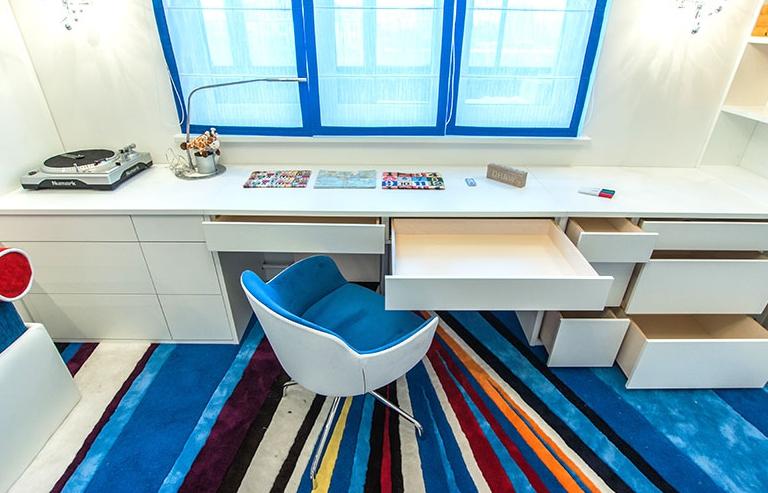 Стильная белая мебель, состоящая из нескольких элементов и расположенная у окна, выглядит стильно и интересно за счет ярких акцентов вокруг