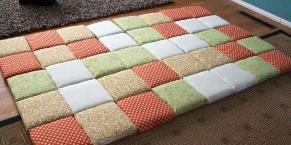 Изголовье кровати, набранное из подушек, отлично подходит для этно-стилей.