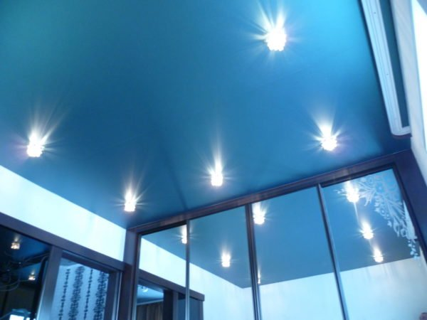 Комната с натяжным потолком выглядит эффектно, только если правильно состыковать полотно со встроенной мебелью.
