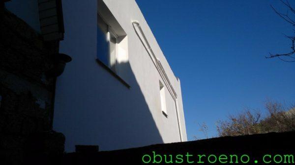 На фото - фасад дома, отделанного шпатлевкой на белом цементе.