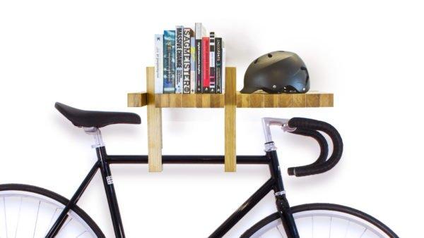 На фото — книжная полка, от которой вниз отходит два зацепа для крепежа велосипеда