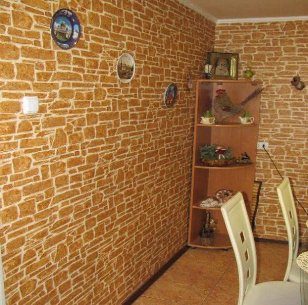 Образцом обоев под камень эффектно выделила угол кухни, как на фото.