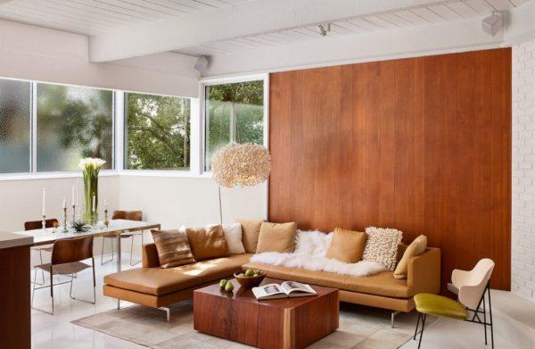 Однотонная деревянная облицовка над диваном в гостиной.