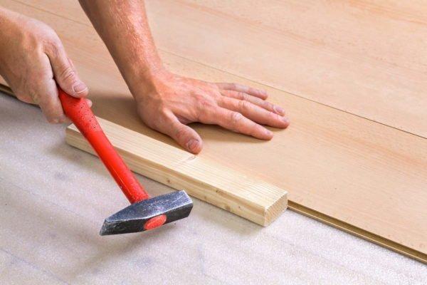 Оставшиеся между досками щели убираются с помощью молотка и бруска из твердой древесины.