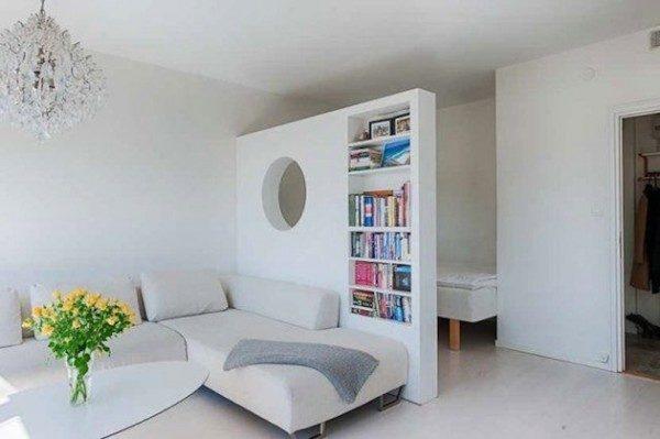 Отделяя нишу с кроватью от гостиной, перегородка одновременно выполняет функцию книжного шкафа