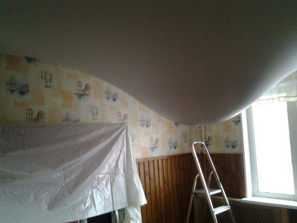 Перед тем, как спустить воду с натяжного потолка, накройте мебель влагонепроницаемой плёнкой