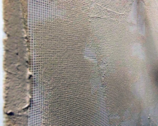 При большой толщине отделки лучше шпаклевать стены по сетке. Она уменьшит вероятность появления трещин.