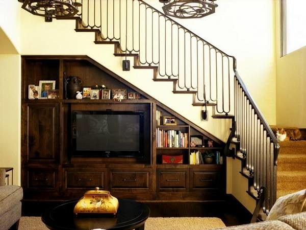 При грамотном подходе пространство под лестницей на второй этаж превращается в красивую и высоко функциональную часть интерьера.