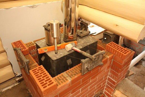 Процесс обкладывания металлической печки облицовочным кирпичом.