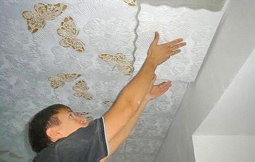 Процесс оклеивания потолка элементами из пенопласта.