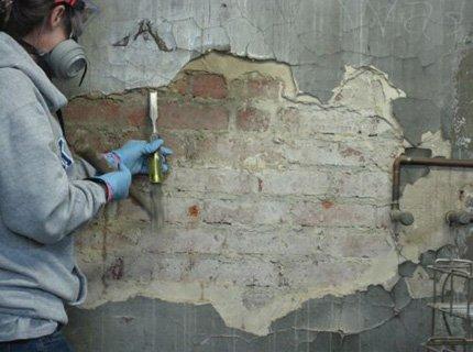 Сбиваем старую штукатурку зубилом и молотком со стены.