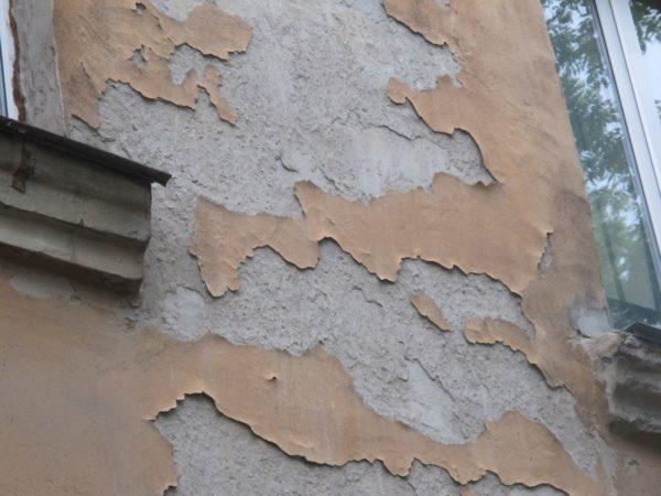 Слабое сцепление с основанием привело к разрушению отделки фасада.