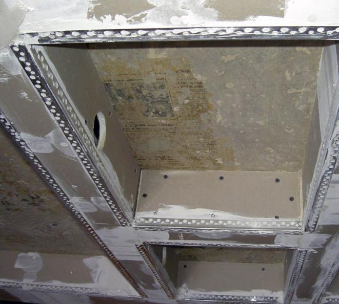 Сложная конструкция из гипсокартона с полками. Все угловые стыки замаскированы металлическими уголками, защищающими торцы листов ГКЛ от повреждений