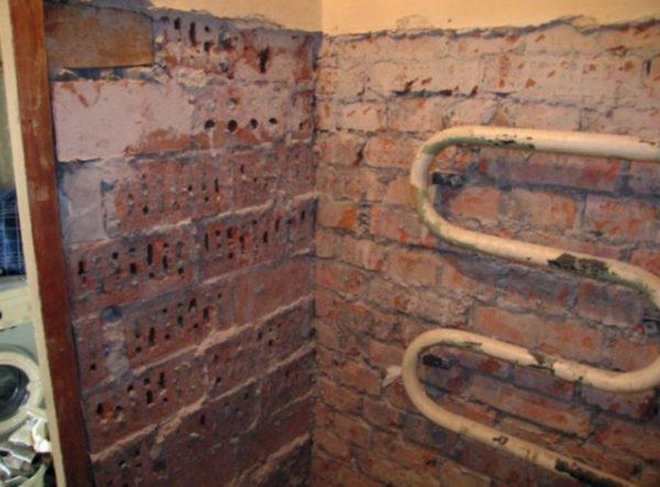 Стена зачищена от краски и штукатурки до кирпичной кладки.