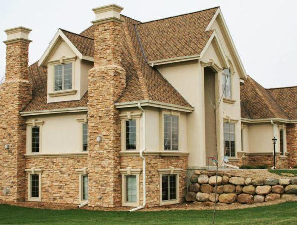 Стилизация современного дома под старинную усадьбу с помощью каменной облицовки.