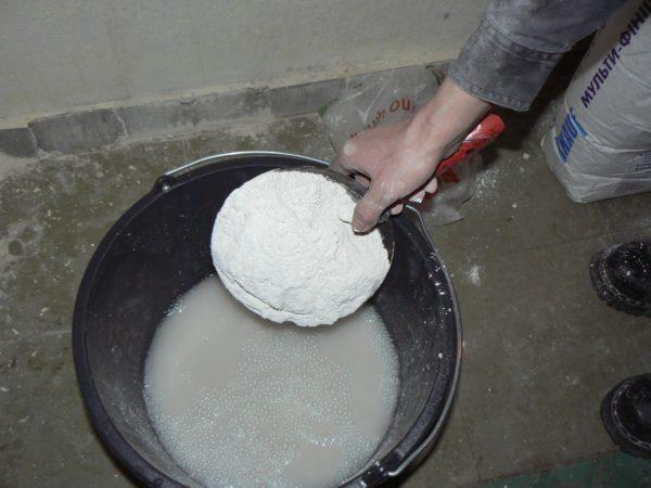Сухая гипсовая смесь засыпается в емкость с уже набранной водой.