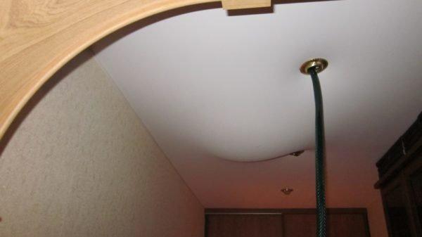 Так выглядит выкачка воды из натяжного потолка через отверстие, созданного монтажниками под осветительный прибор