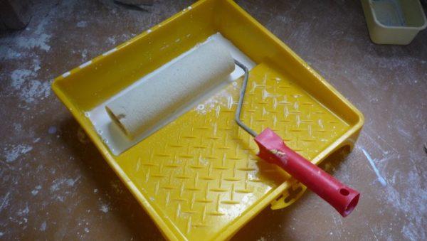 Валик окунается в грунтовку и отжимается на решетке — так вы экономите состав
